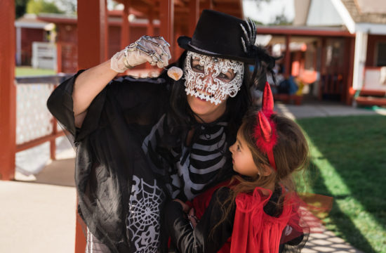 A woman in a lace skeleton mask and skeleton costume helps a young girl dressed like a devil to reach a donut hole hanging on a string.