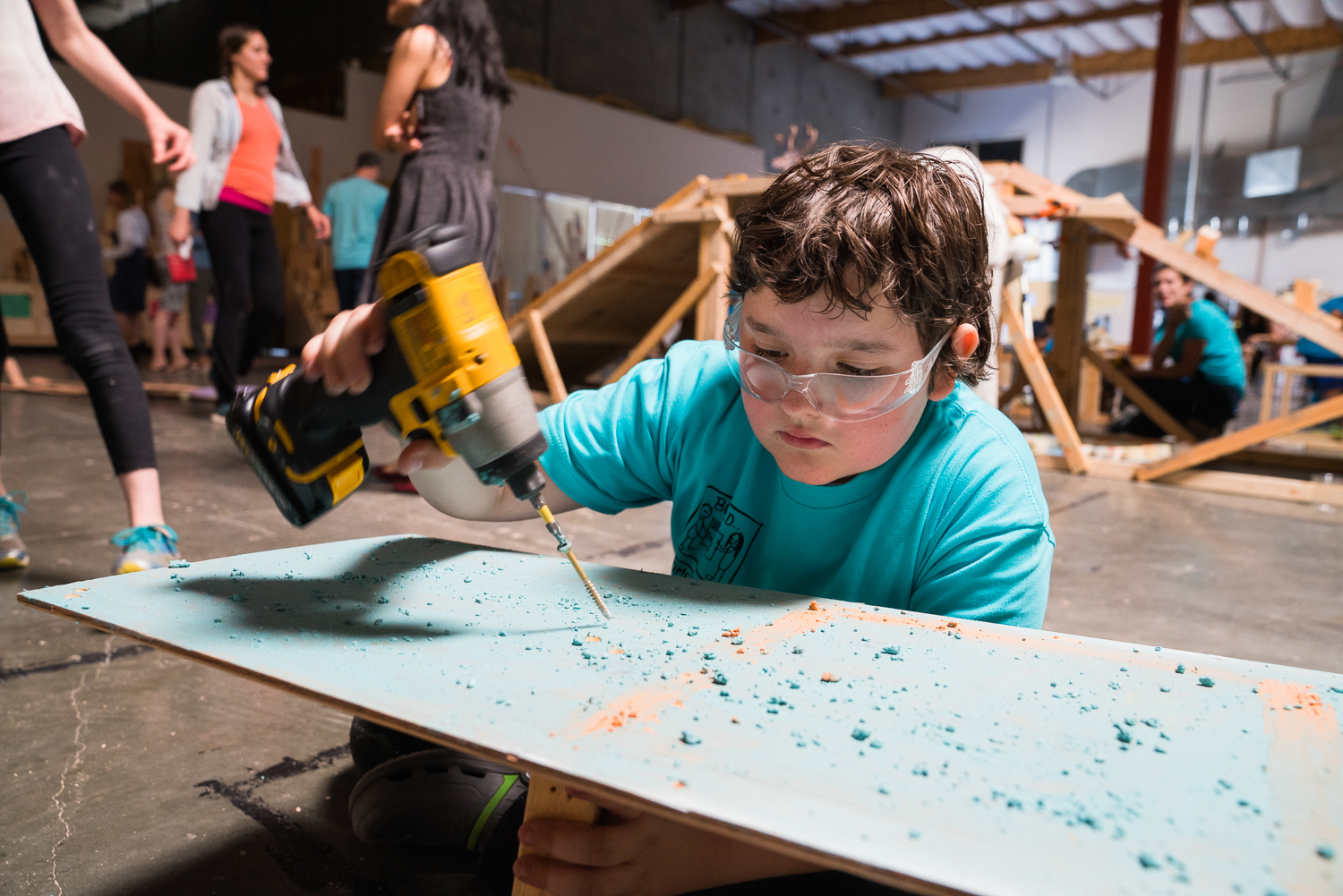 A boy wearing goggles works with a power screwdriver and a wooden board.