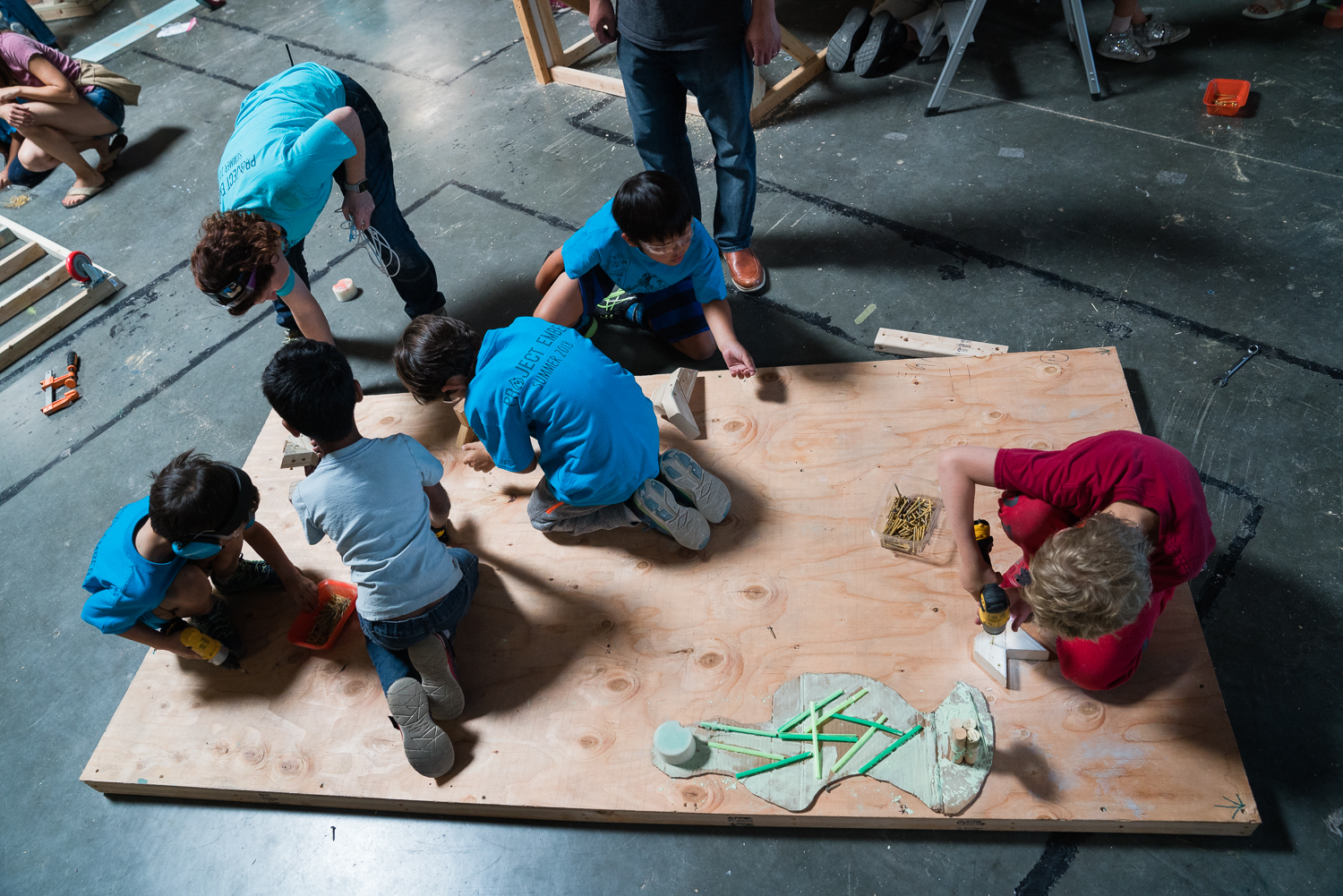 A group of kids kneel and work with power screwdrivers on a large sheet of plywood which lies on the floor.