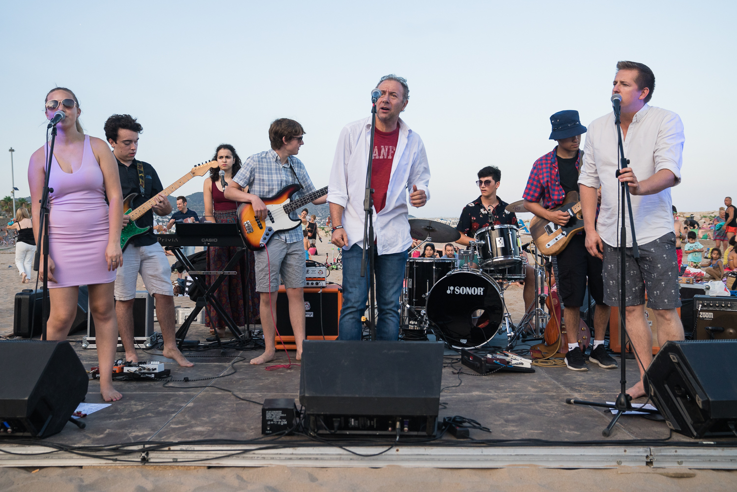 A band plays on a beach stage.