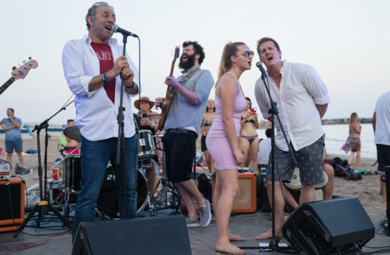 Four band members sing on a stage on the beach.